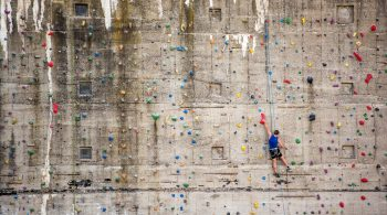 Rostock, Germany - May 27, 2016: A man boulder on a climbing wall in Rostock. The wall is part of an old bunker near the baltic sea.